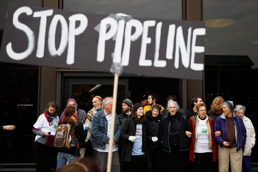 Protesters demonstrating in opposition to the proposed Keystone XL oil pipeline, Monday, March 10, 2014, block the door to the federal building in Philadelphia. The protesters say the pipeline would contribute to global warming. (AP Photo/Matt Rourke)