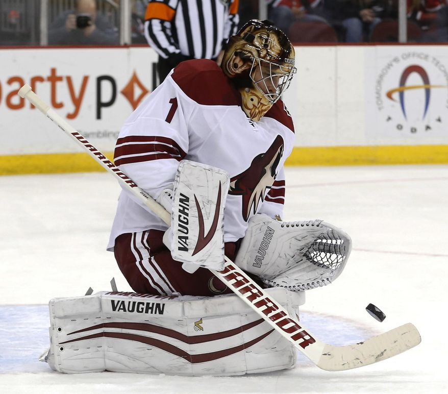 Phoenix Coyotes goalie Thomas Greiss, of Germany, makes a save on a shot by the New Jersey Devils during the second period of an NHL hockey game, Thursday, March 27, 2014, in Newark, N.J. (AP Photo/Julio Cortez)