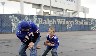 FILE - In this Nov. 17, 2013, file photo, Rich Stifter, Jr., takes the snap from his dad Rich Stifter, Sr., in the parking lot of Ralph Wilson Stadium before his first NFL football game between the Buffalo Bills and the New York Jets in Orchard Park, N.Y. Bills owner Ralph Wilson Jr. has died at his home in Grosse Pointe Shores, Mich., Tuesday, March 25, 2014. He was 95. Bills president Russ Brandon made the announcement at the NFL winter meetings in Orlando, Fla. Wilson Jr. was one of the original founders of the American Football League and owned the Bills for the last 54 years. (AP Photo/Gary Wiepert, File)