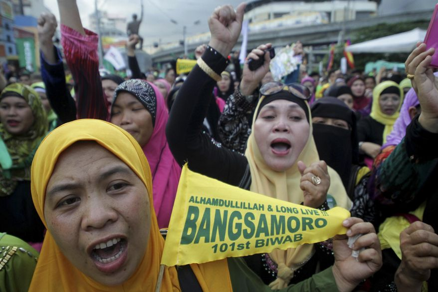 Filipino Muslims cheer after learning that a peace accord has been signed between Moro Islamic Liberation Front leaders and Philippine President Benigno Aquino III during a rally Thursday March 27, 2014 outside the presidential palace in Manila, Philippines. The Philippine government signed a peace accord with the country's largest Muslim rebel group on Thursday, the culmination of years of negotiations and a significant political achievement for President Benigno Aquino III. (AP Photo)