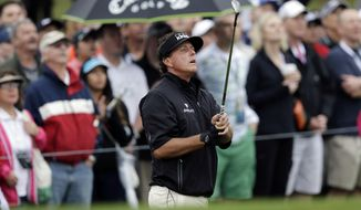 Phil Mickelson watches his chip shot on the 10th hole during the first round of the Valero Texas Open golf tournament, Thursday, March 27, 2014, in San Antonio. Play was delayed for more than two hours Thursday due to rain and fog. (AP Photo/Eric Gay)