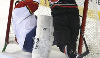Carolina Hurricane's Radek Dvorak (18) slams into Florida Panthers goalie Roberto Luongo, left, during the first period of an NHL hockey game in Sunrise, Fla., Thursday, March 27, 2014. (AP Photo/J Pat Carter)