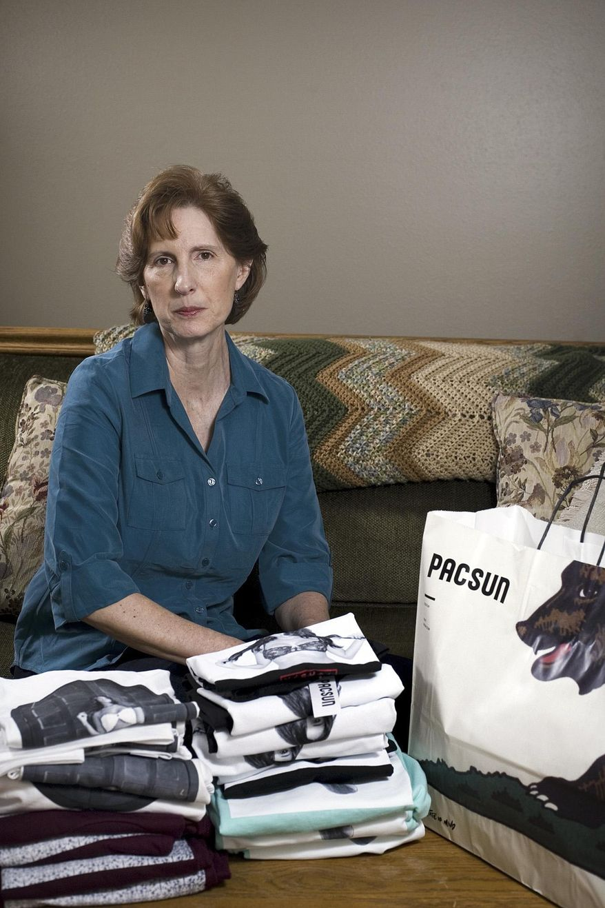 "FILE - This Feb. 17, 2014, file photo shows Judy Cox sitting next to a stack of T-shirts with what she believes are pornographic designs in Orem, Utah. Cox purchased the entire stock of T-shirts from the PacSun store in Orem believing their display broke Orem's decency code. Cox said she complained about the window display to a store manager and was told the T-shirts couldn't be taken down without approval from the corporate office. A conservative Utah city that decided it likely would lose a legal battle over a national clothing store's ""offensive"" mall display of T-shirts has instead sent the company a scathing letter. The letter from city officials in Orem, was a show of support for Cox.  (AP Photo/The Daily Herald, Mark Johnston, file)"