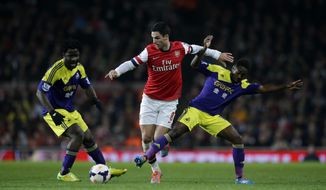 Arsenal's Mikel Arteta, center, competes for the ball with Swansea City's Nathan Dyer, right, and Wilfried Bony during the English Premier League soccer match between Arsenal and Swansea City's at the Emirates Stadium in London, Tuesday, March 25, 2014.  (AP Photo/Matt Dunham)