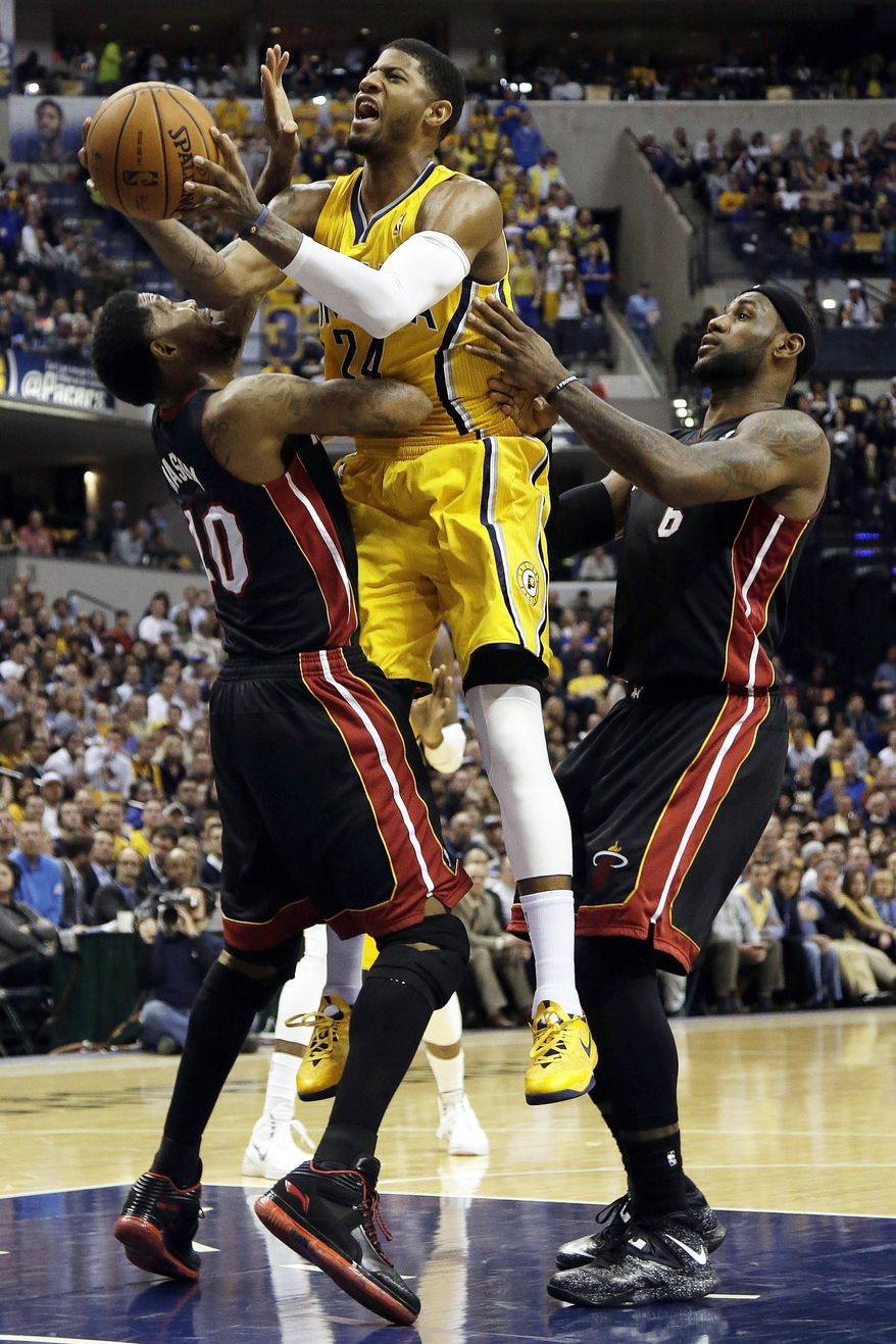 Indiana Pacers forward Paul George, center, shoots between Miami Heat defenders Udonis Haslem, left, and LeBron James during the second half of an NBA basketball game in Indianapolis, Wednesday, March 26, 2014. The Pacers won 84-83. (AP Photo/AJ Mast)