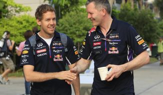 Red Bull driver Sebastian Vettel, left, of Germany is greeted by his crew member as he arrives at the paddock for a practice session ahead of the Malaysian Formula One Grand Prix at Sepang International Circuit in Sepang, Malaysia, Friday, March 28, 2014. (AP Photo/Peter Lim)