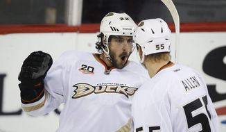 Anaheim Ducks' Mathieu Perreault, left, celebrates his game tying goal with teammate Bryan Allen during third period NHL hockey action against the Calgary Flames in Calgary, Alberta, Wednesday, March 26, 2014. The Anaheim Ducks beat the Calgary Flames 3-2.(AP Photo/The Canadian Press, Jeff McIntosh)
