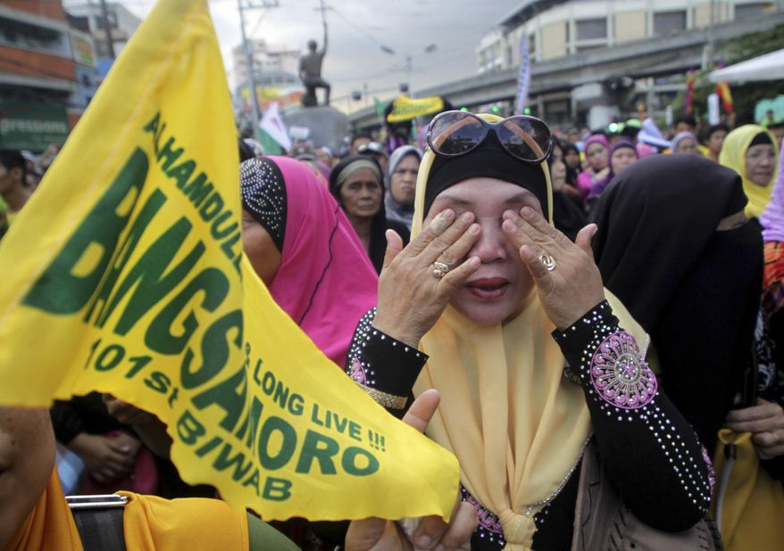Filipino Muslims wipe their tears after learning that a peace accord has been signed between Moro Islamic Liberation Front leaders and Philippine President Benigno Aquino III during a rally Thursday March 27, 2014 outside the presidential palace in Manila, Philippines. The Philippine government signed a peace accord with the country's largest Muslim rebel group on Thursday, the culmination of years of negotiations and a significant political achievement for Aquino. (AP Photo)