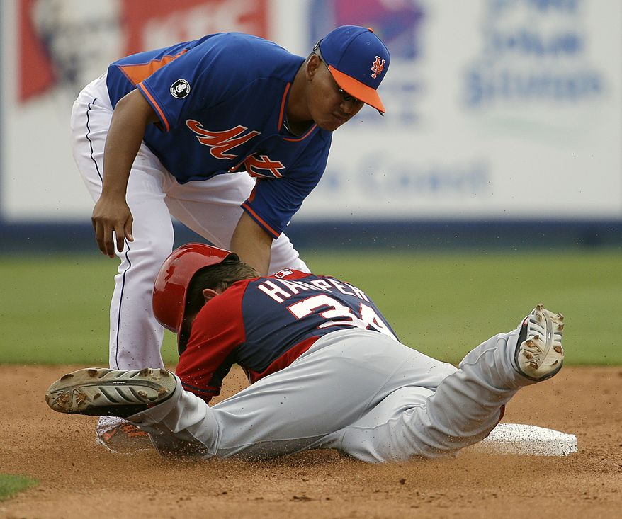 Washington Nationals' Bryce Harper, bottom, is tagged out at second base by New York Mets' Ruben Tejada on a steal attempt in the sixth inning of an exhibition spring training baseball game, Thursday, March 27, 2014, in Port St. Lucie, Fla. (AP Photo/David Goldman)