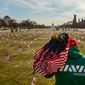 Veteran Army Spc. Julio Bernal of Takoma Park, Md. who served in Iraq brings more American flags over to fellow military veterans who put them down on the National Mall in D.C. on March 27, 2014. Veterans and supporters place American flags on the National Mall to represent each of the 1,892 veterans and service members who have died by suicide this year. (The Washington Times) **FILE**