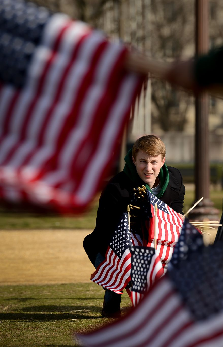 Army Veteran Sgt. Nick McCormick of Washington, D.C. helps line up a row of flags on the National Mall, Washington, D.C., Thursday, March 27, 2014. Veterans and supporters place American flags on the National Mall to represent each of the 1,892 veterans and service members who have died by suicide this year. (Andrew Harnik/The Washington Times)