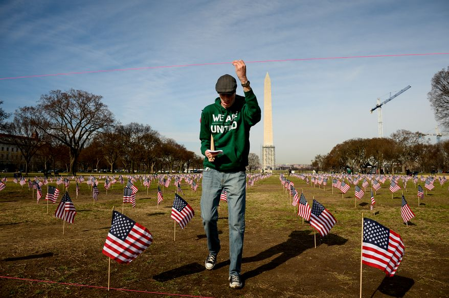 Veteran Marine Cpl. Aaron Mankin who served in Iraq helps fellow military veterans line up rows of American flags on the National Mall, Washington, D.C., Thursday, March 27, 2014. Veterans and supporters place American flags on the National Mall to represent each of the 1,892 veterans and service members who have died by suicide this year. (Andrew Harnik/The Washington Times)