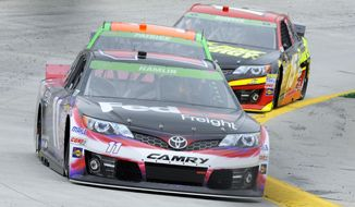 Sprint Cup driver Denny Hamlin (11) leads Danica Patrick and Clint Bowyer through turn four during the first round of practice for a NASCAR auto race at Martinsville Speedway in Martinsville, Va., Friday March 28, 2014. (AP Photo/Mike McCarn)