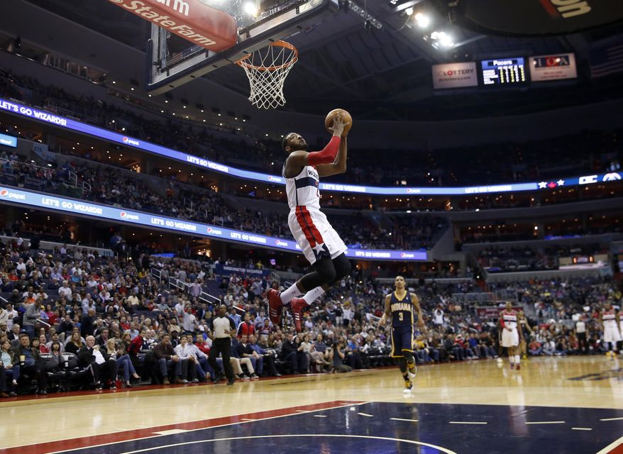 Washington Wizards guard John Wall dunks in the first half of an NBA basketball game against the Indiana Pacers, Friday, March 28, 2014, in Washington. (AP Photo/Alex Brandon)
