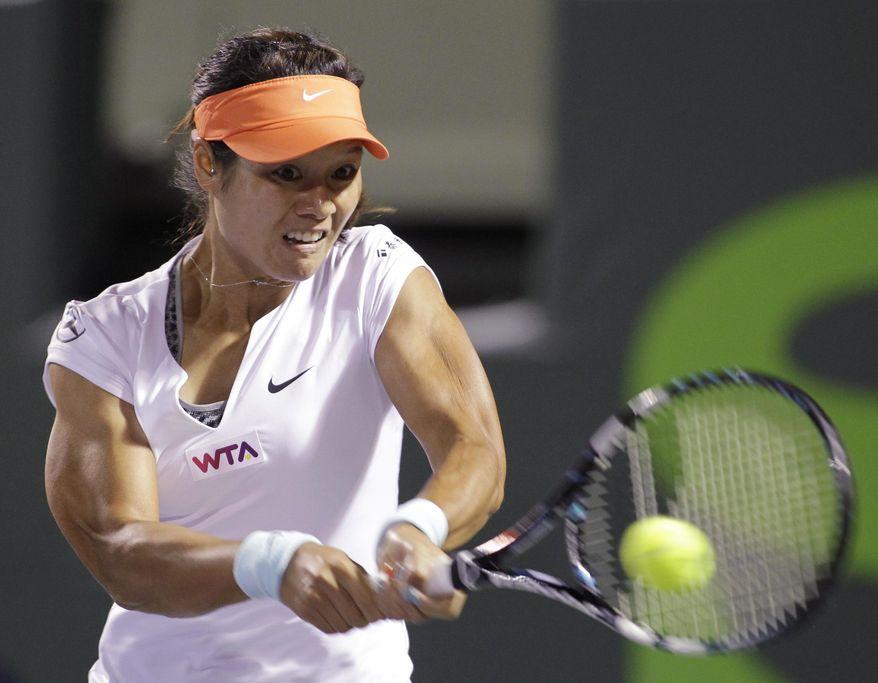Li Na, of China, returns the ball to Dominika Cibulkova, of Slovakia, during the Sony Open tennis tournament, Thursday, March 27, 2014, in Key Biscayne, Fla. (AP Photo/Luis M. Alvarez)