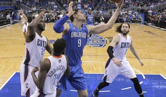 Orlando Magic's Nikola Vucevic (9) grabs an offensive rebound in front of Charlotte Bobcats' Al Jefferson, left, Michael Kidd-Gilchrist (14) and Josh McRoberts, right, during the first half of an NBA basketball game in Orlando, Fla., Friday, March 28, 2014. (AP Photo/John Raoux)