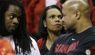Former U.S. Secretary of State Condoleezza Rice, center watches play between Dayton and Stanford during the first half in a regional semifinal game at the NCAA college basketball tournament, Thursday, March 27, 2014, in Memphis, Tenn. (AP Photo/Mark Humphrey)