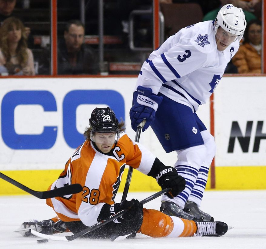 Philadelphia Flyers' Claude Giroux, left, tries to pass the puck after a collision with Toronto Maple Leafs' Dion Phaneuf during the first period of an NHL hockey game, Friday, March 28, 2014, in Philadelphia. (AP Photo/Matt Slocum)