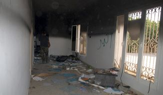 """FILE - This Sept. 12, 2012 file photo shows a man walking through a room in the gutted U.S. consulate in Benghazi, Libya, after an attack that killed four Americans, including Ambassador Chris Stevens. Rep. Darrell Issa, R-Calif. is doggedly pursuing the question of whether military personnel were told to """"stand down"""" during the 2012 deadly assault on the U.S. diplomatic mission in Benghazi, Libya, despite the insistence of military leaders and other Republicans that it never happened. (AP Photo/Ibrahim Alaguri, File)"""