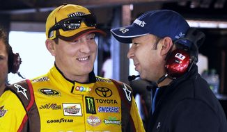 NASCAR Sprint Cup driver Kyle Busch, left, talks with Chad Knaus, prior to practice at Martinsville Speedway in Martinsville, Va., Friday March 28, 2014. (AP Photo/Mike McCarn)