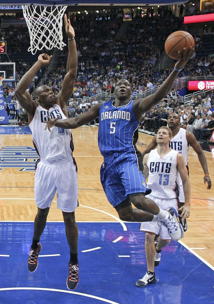Orlando Magic's Victor Oladipo (5) drives to the basket for a shot past Charlotte Bobcats' Bismack Biyombo, left, Luke Ridnour (13) and Anthony Tolliver, right, during the first half of an NBA basketball game in Orlando, Fla., Friday, March 28, 2014. (AP Photo/John Raoux)