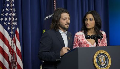 """FILE - In this Wednesday, March 19, 2014 file photo, Diego Luna, left, and Rosario Dawson stand behind the podium after President Barack Obama spoke at the screening of the film """"Cesar Chavez,"""" in the Old Executive Office Building on the White House complex in Washington. Luna directed the movie biopic about the Mexican-American labor leader Chavez, that features Dawson as Dolores Huerta, the renowned civil rights activist. (AP Photo/Pablo Martinez Monsivais, file)"""