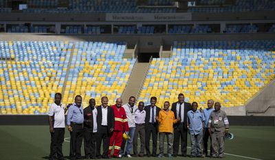 Brazil's former soccer star Zico, forth from left, former soccer players and members of the local organizing committee for the 2014 World Cup, Bebeto, center, and Ronaldo, forth from right, pose for a photo with workers of the 2014 World Cup stadiums after a news conference at the Maracana stadium in Rio de Janeiro, Brazil, Thursday, March 27, 2014. (AP Photo/Felipe Dana)