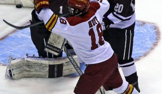 Ferris State forward Andy Huff (18) celebrates after getting an assist on a goal against Colgate goalie Charlie Finn (1) and defenseman Brett Corkey (20) in the first period of a regional semifinal game of the NCAA college hockey tournament, Friday, March 28, 2014, in Cincinnati. (AP Photo/Al Behrman)