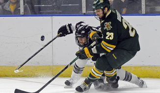 Vermont's Connor Brickley (23) and Union's Mat Brodie fight for a loose puck during the second period during a game in the men's NCAA East Regional hockey tournament Friday, March 28, 2014, in Bridgeport, Conn.