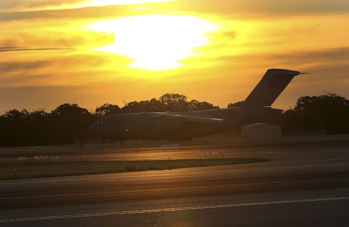 Royal Australia Air Force C-17 lands at RAAF Base Pearce to deliver a Sea Hawk helicopter to help with the search for the missing Malaysia Airlines Flight MH370, in Perth, Australia, Friday, March 28, 2014. Australian officials moved the search area for the lost Malaysian jetliner 1,100 kilometers (680 miles) to the northeast Friday, following a new analysis of radar data, and a plane quickly found objects that a ship set out to investigate. (AP Photo/Rob Griffith)
