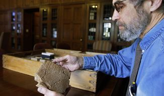 FILE - In this Oct. 16, 2008 file photo, Matt Stolper, director of the Persepolis Fortification Archive at the University of Chicago's Oriental Institute, examines a tablet that is part of a collection that provide a top-to-bottom look at life in the Persian empire 2,500 years ago. On Friday, March 28, 2014, a federal judge in Chicago ruled that survivors of a 1997 terrorist attack blamed partly on Iran can't seize museum pieces in U.S. collections to help pay a $412 million judgment against Iran. The ruling stems from a long-running legal battle that museum officials elsewhere watching closely. They feared their own collections could be put at risk if the judge had allowed collections of Persian antiquities at Chicago's Field Museum and the University of Chicago to be seized. (AP Photo/M. Spencer Green, File)