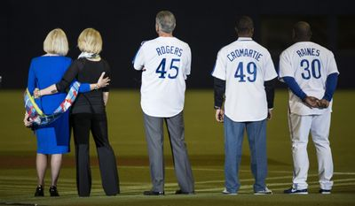 Sandy Carter, left, wife of former Montreal Expos Gary Carter, her daughter Kiimy, second left, and former Expos Steve Roger, Warren Cromartie and Tim Raines watch a video on the giant screen prior to a pre-season game between the Toronto Blue Jays and the New York Mets Friday, March 28, 2014 in Montreal.(AP Photo/The Canadian Press, Paul Chiasson)