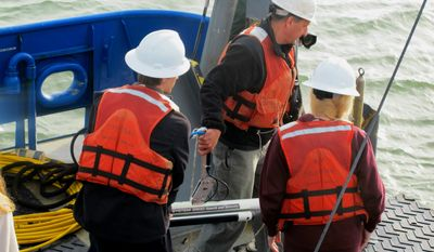 In this March 20, 2014 photo, Scott Harris, center, an associate professor in the department of geology and environmental geosciences at the College of Charleston, deploys a sidescan sonar unit with two students from the college from the back of the research vessel Savannah in Charleston Harbor in Charleston, S.C. Students aboard the vessel completed several days of mapping the mid-intercontinental shelf off South Carolina. (AP Photo/Bruce Smith)