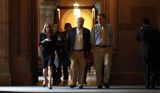 Senate Republican leader Dean Skelos, R-Rockville Centre, center, walks to a legislative leaders budget meeting at the Capitol on Friday, March 28, 2014, in Albany, N.Y. (AP Photo/Mike Groll)
