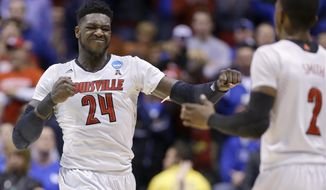 Louisville's Montrezl Harrell (24) reacts with Russ Smith (2) during the first half of an NCAA Midwest Regional semifinal college basketball tournament game against the Kentucky Friday, March 28, 2014, in Indianapolis. (AP Photo/Michael Conroy)