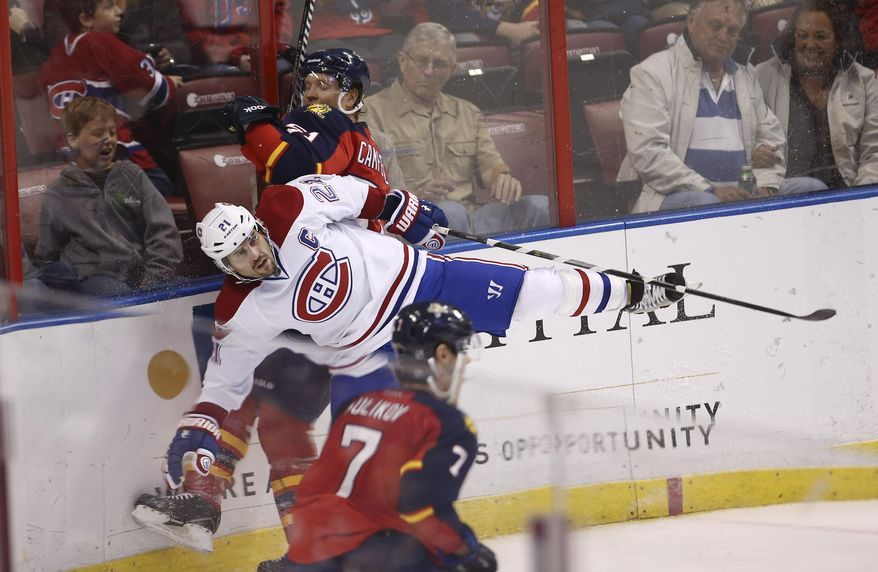 Montreal Canadiens' Brian Gionta (21) and Florida Panthers' Brian Campbell (51) slam into the baords during the second period of an NHL hockey game in Sunrise, Fla., Saturday, March 29, 2014. (AP Photo/J Pat Carter)
