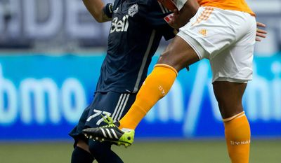 Houston Dynamo's Jermaine Taylor, right, of Jamaica, heads the ball away from Vancouver Whitecaps' Pedro Morales, of Chile, during the second half of an MLS soccer game in Vancouver, British Columbia, Saturday, March 29, 2014. (AP Photo/The Canadian Press, Darryl Dyck)