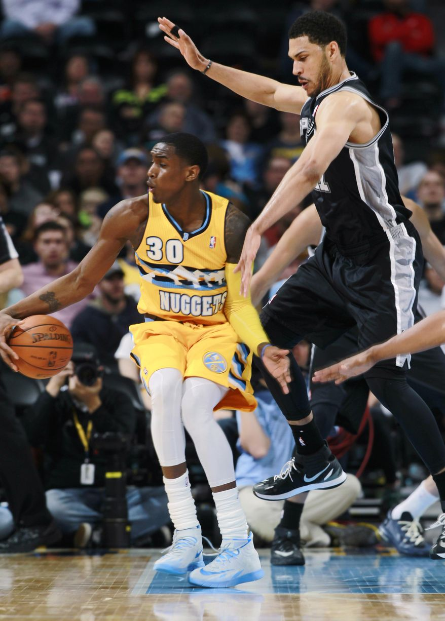 Denver Nuggets forward Quincy Miller, left, picks up loose ball as San Antonio Spurs forward Jeff Ayers defends in the fourth quarter of the Spurs' 133-102 victory in an NBA basketball game in Denver on Friday, March 28, 2014. (AP Photo/David Zalubowski)