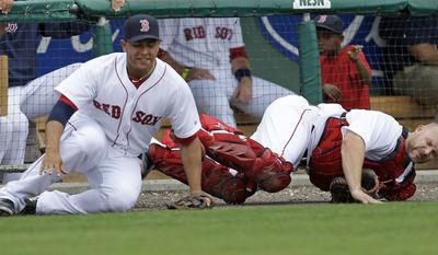 Boston Red Sox catcher David Ross, right, and third baseman Carlos Rivero collide while chasing a pop foul by Minnesota Twins' Josh Willingham during the sixth inning of an exhibition baseball game in Fort Myers, Fla., Saturday, March 29, 2014. (AP Photo/Gerald Herbert)