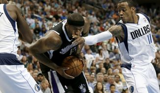 Dallas Mavericks' Samuel Dalembert , left, of Haiti, helps defend as Sacramento Kings' DeMarcus Cousins (15) takes a hand to the face from the Mavericks' Monta Ellis, right, in the first half of an NBA basketball game, Saturday, March 29, 2014, in Dallas. (AP Photo/Tony Gutierrez)