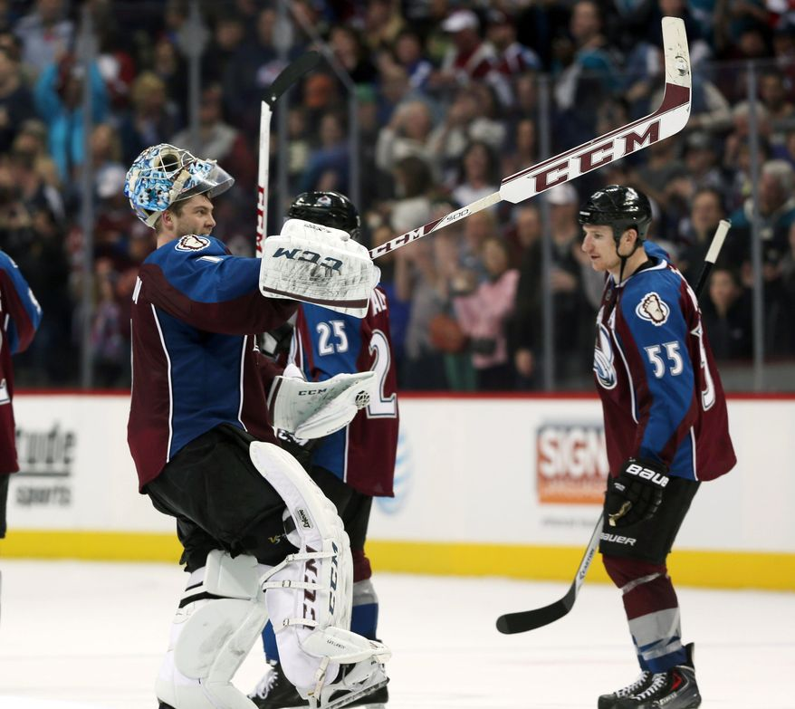 Colorado Avalanche goalie Semyon Varlamov, front, of Russia, celebrates as left wing Cody McLeod looks on after the Avalanche's 3-2 victory over the San Jose Sharks in an NHL hockey game in Denver on Saturday, March 29, 2014. Varlamov had a season-high 47 saves and the Avalanche clinched their first playoff berth in four years. (AP Photo/David Zalubowski)