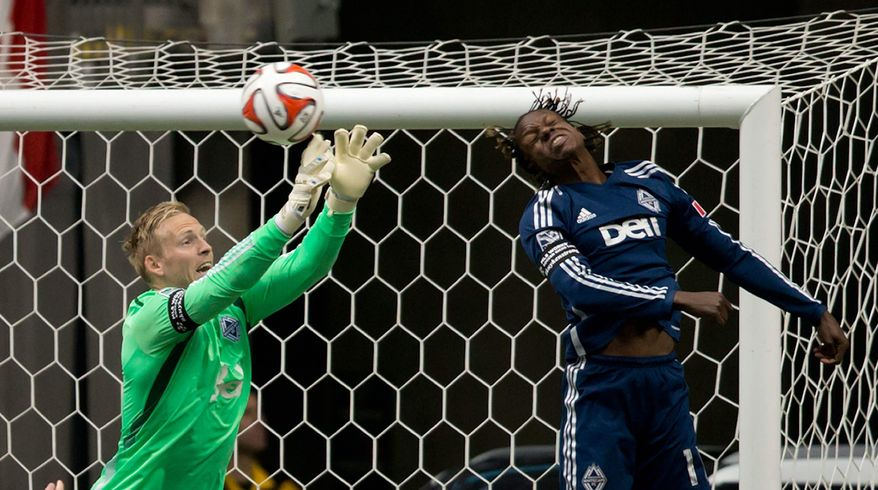 Vancouver Whitecaps' goalkeeper David Ousted, left, of Denmark, makes a save as teammate Darren Mattocks, of Jamaica, also defends during the first half of an MLS soccer game in Vancouver, British Columbia, Saturday, March 29, 2014. (AP Photo/The Canadian Press, Darryl Dyck)
