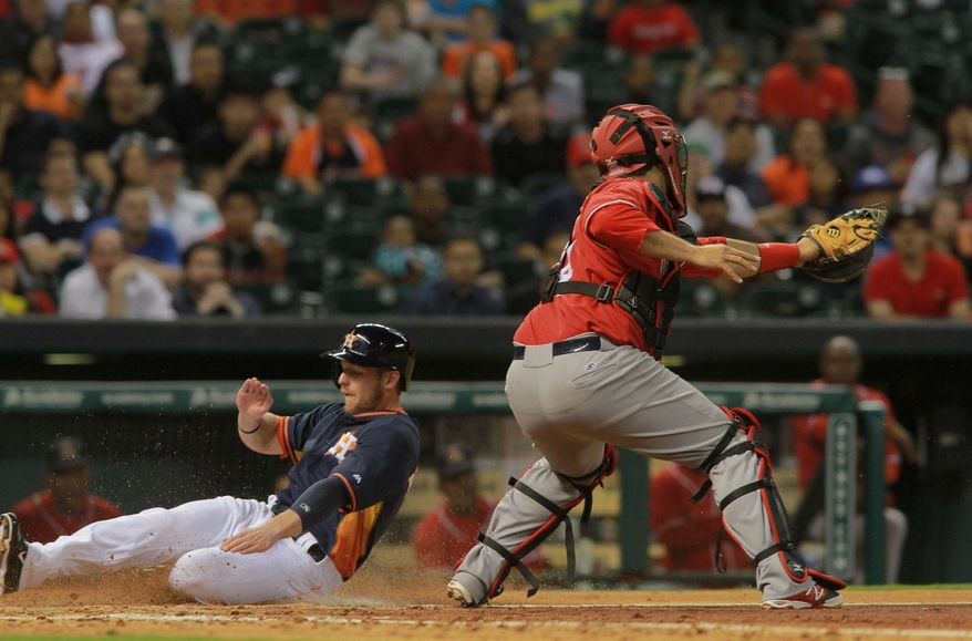 Houston Astros' Alex Presley, left, scores ahead of the throw to Rojos del Aguila de Veracruz catcher Humberto Sosa in the fourth inning of a spring exhibition baseball game on Saturday, March 29, 2014, in Houston. (AP Photo/Richard Carson)