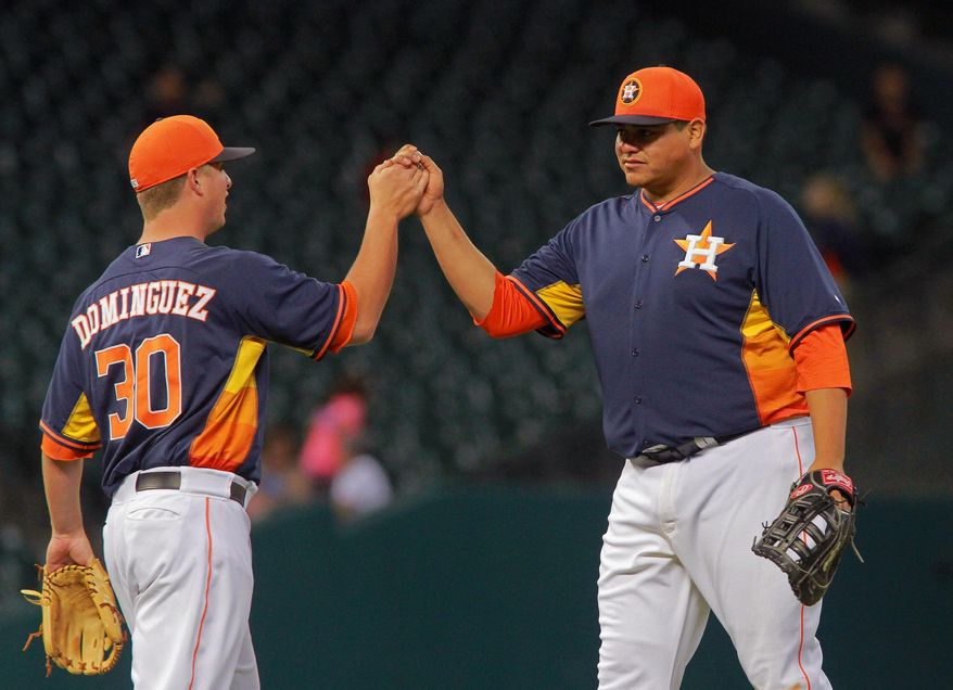 Houston Astros' Matt Dominguez and Japet Amador celebrate after defeating Rojos del Aguila de Veracruz 2-0 in a spring exhibition baseball game on Saturday, March 29, 2014, in Houston. (AP Photo/Richard Carson)