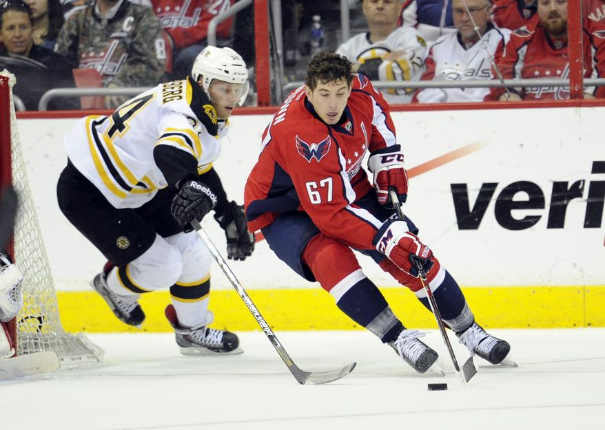 Washington Capitals center Chris Brown (67) skates with the puck against Boston Bruins center Carl Soderberg (34), of Sweden, during the second period of an NHL hockey game, Saturday, March 29, 2014, in Washington. (AP Photo/Nick Wass)
