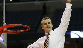 Florida head coach Billy Donovan holds the net after the second half in a regional final game against Dayton at the NCAA college basketball tournament, Saturday, March 29, 2014, in Memphis, Tenn. Florida won 62-52. (AP Photo/John Bazemore)