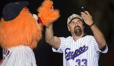"""Former Montreal Expos Larry Walker shoots a """"selfie"""" with mascot Youppi as members of the 1994 team are introduced prior to an exhibition baseball game between the Toronto Blue jays and the New York Mets Saturday, March 29, 2014, in Montreal. (AP Photo/The Canadian Press, Paul Chiasson)"""