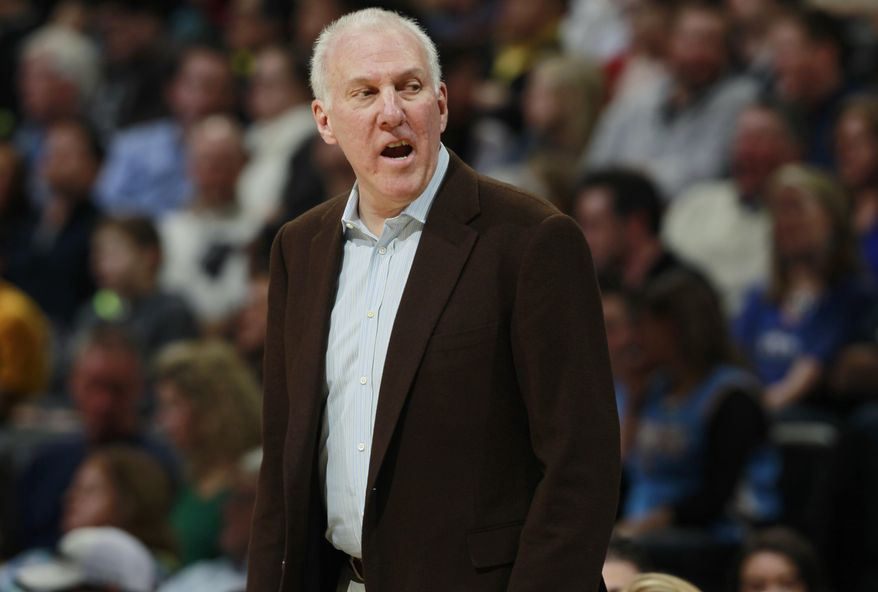 San Antonio Spurs coach Gregg Popovich calls to players on the bench for a replacement against the Denver Nuggets in the fourth quarter of the Spurs' 133-102 victory in an NBA basketball game in Denver on Friday, March 28, 2014. (AP Photo/David Zalubowski)