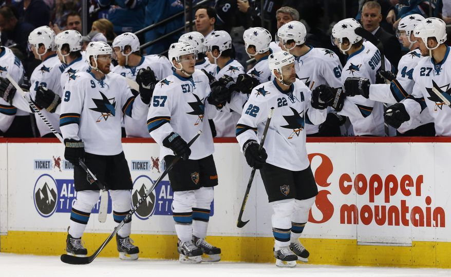 San Jose Sharks defenseman Dan Boyle, front right, is congratulated after scoring a goal as teammates Marty Havlat, of the Czech Republic, front left, and Tommy Wingels follow past the team box while facing the Colorado Avalanche in the second period of an NHL hockey game in Denver on Saturday, March 29, 2014. (AP Photo/David Zalubowski)
