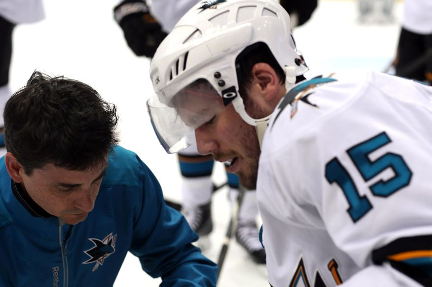 San Jose Sharks left wing James Sheppard, right, is helped off the ice after being injured while pursuing the puck with Colorado Avalanche left wing Jamie McGinn in the second period of an NHL hockey game in Denver on Saturday, March 29, 2014. (AP Photo/David Zalubowski)
